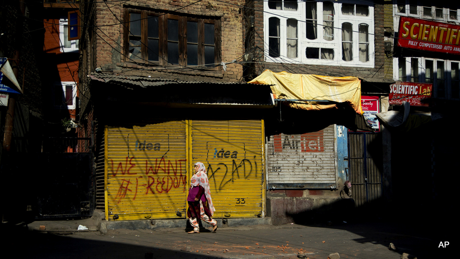 A Kashmiri woman walks on a road dotted with bricks and stones after a protest during curfew in Srinagar, Indian occupied Kashmir, Friday, Sept. 30, 2016.