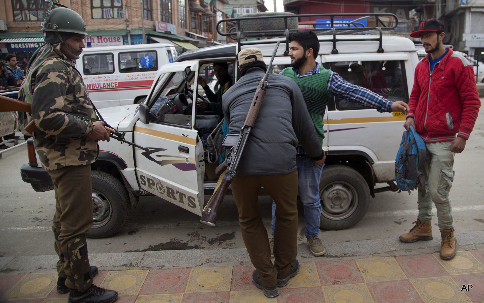 An Indian police man frisks a Kashmiri youth as an Indian paramilitary soldier, left, stands guard at a temporary checkpoint in Srinagar, Indian occupied Kashmir, Wednesday, Nov. 4, 2015.