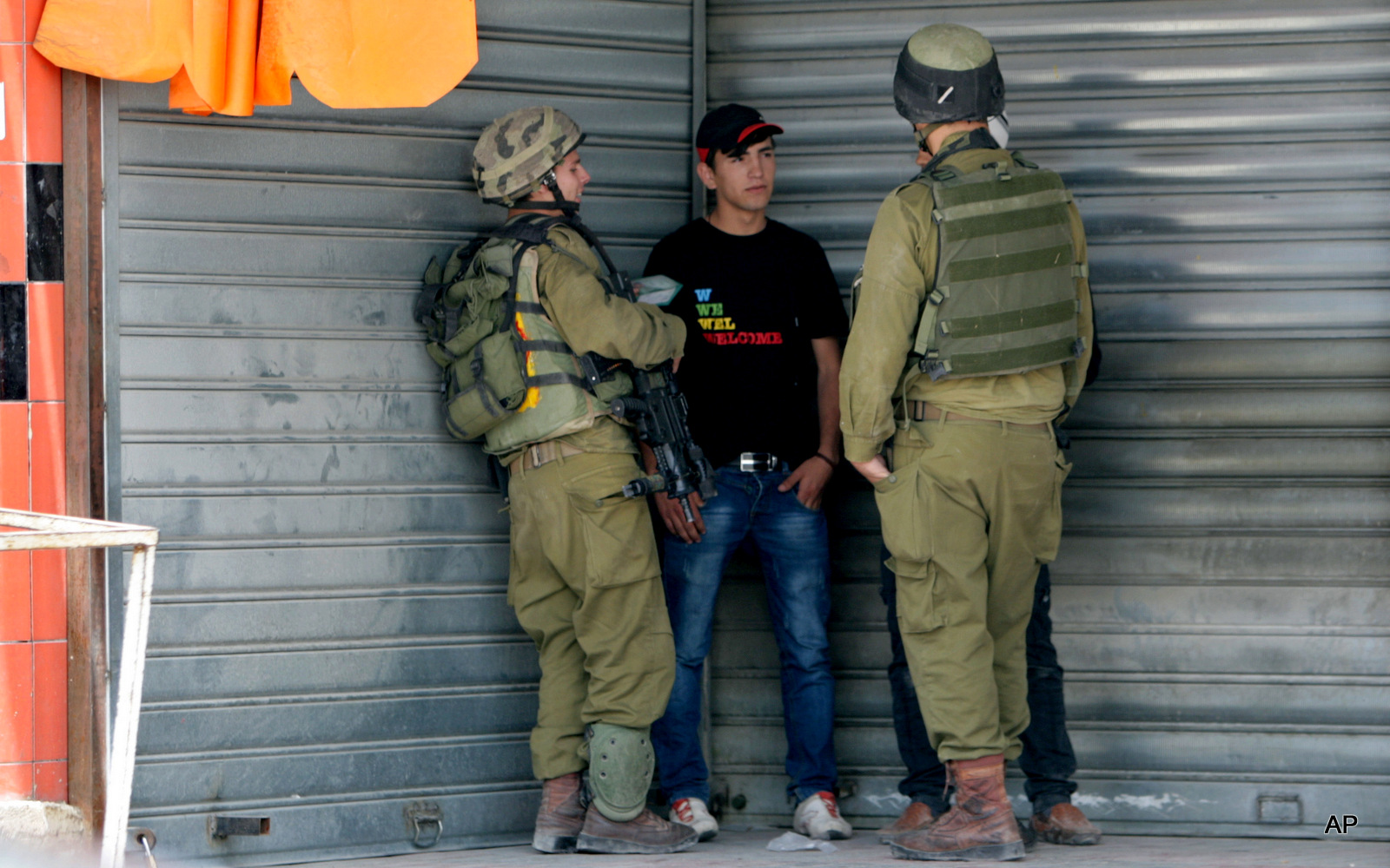 Israeli soldiers check the IDs of Palestinians near an Israeli checkpoint near Nablus, in the Israeli occupied West Bank, Tuesday, June 3, 2014.
