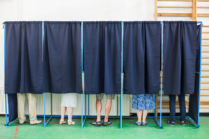 58315392 - color image of some people voting in some polling booths at a voting station.
