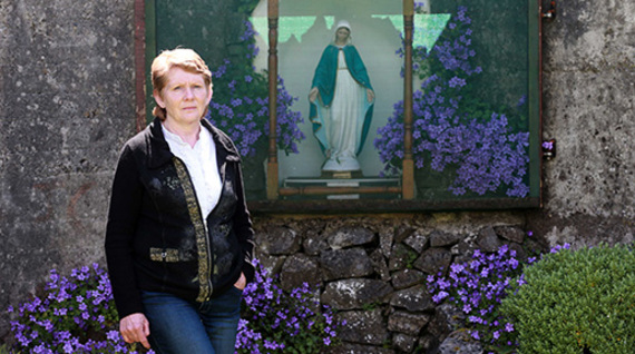 Historan Catherine Corless standing before the grotto in Tuam, Galway.