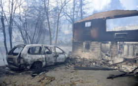 A home and vehicle are damaged from the wildfires around Gatlinburg, Tenn., on Tuesday, Nov. 29, 2016. Rain had begun to fall in some areas, but experts predicted it would not be enough to end the relentless drought that has spread across several Southern states and provided fuel for fires now burning for weeks in states including Tennessee, Georgia and North Carolina. (Michael Patrick/Knoxville News Sentinel via AP)