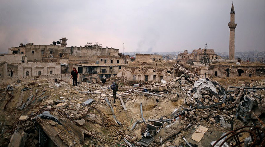 A member of forces loyal to Syria's President Bashar al-Assad stands with a civilian on the rubble of the Carlton Hotel, in the government controlled area of Aleppo, Syria December 17, 2016. © Omar Sanadiki