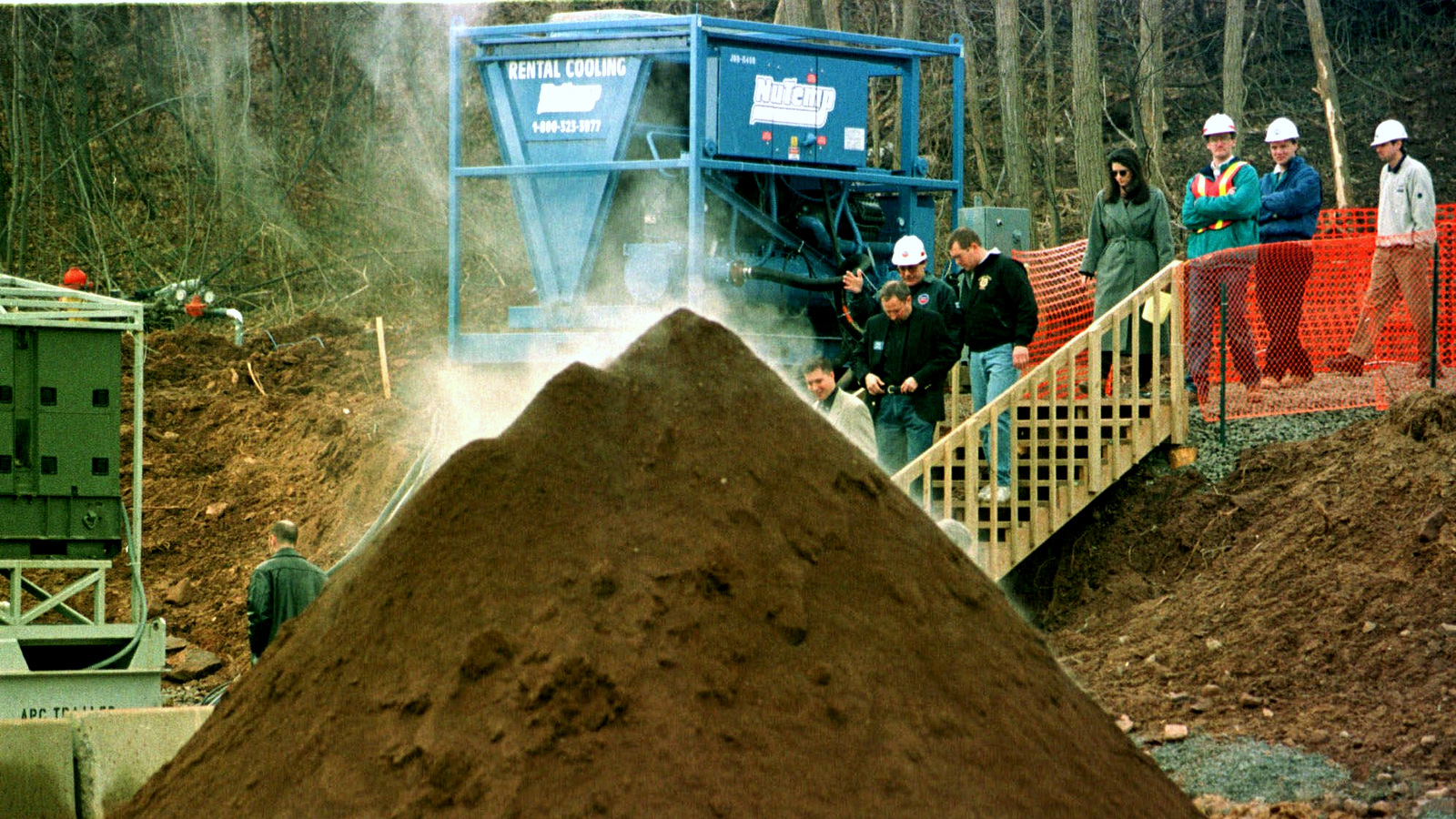 U.S. Environmental Protection Agency officials and visitors walk past a steaming mound of decontaminated soil during a tour of the Industrial Latex Superfund site in Wallington, N.J., Friday, Feb. 12, 1999. (AP Photo/Mike Derer)