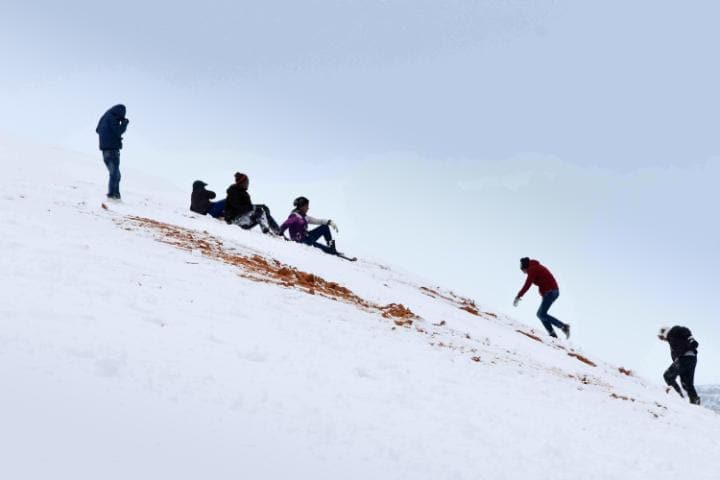 Children sledge down snow covered dunes in the Algerian town Aïn Séfra. Click to enlarge