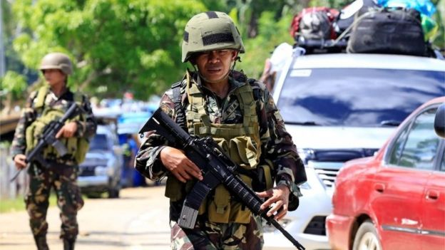 Government troops stand on guard during a checkpoint along a main highway in Pantar town, Lanao del Norte, after residents started to evacuate their hometown of Marawi city, southern Philippines May 24, 2017.