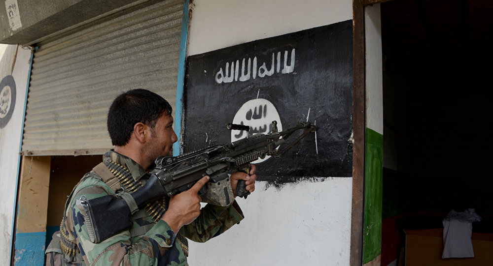 An Afghan soldier points his gun at Daesh militants group banner as he patrols during ongoing clashes in Kot District in eastern Nangarhar province