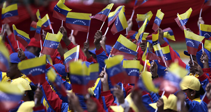 People wave Venezuelan flags during a parade marking 200 years of Venezuela's independence in Caracas, Venezuela, Tuesday July 5, 2011.