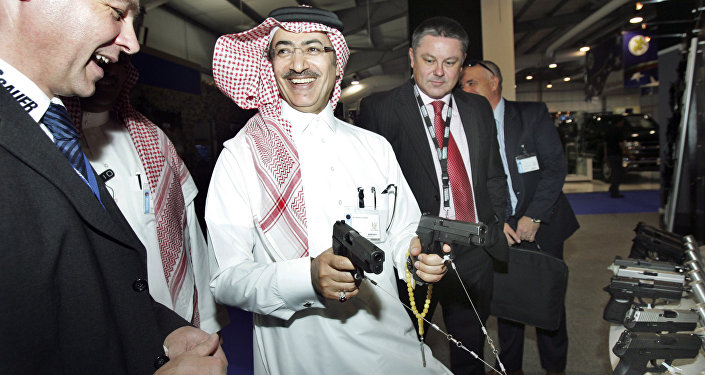 Mahmoud Al-Gahtani of Saudi Arabia, center, inspects guns during the opening of the Special Operations Forces Exhibition and Conference (SOFEX) held at the King Abdullah I airbase located near Amman in Jordan