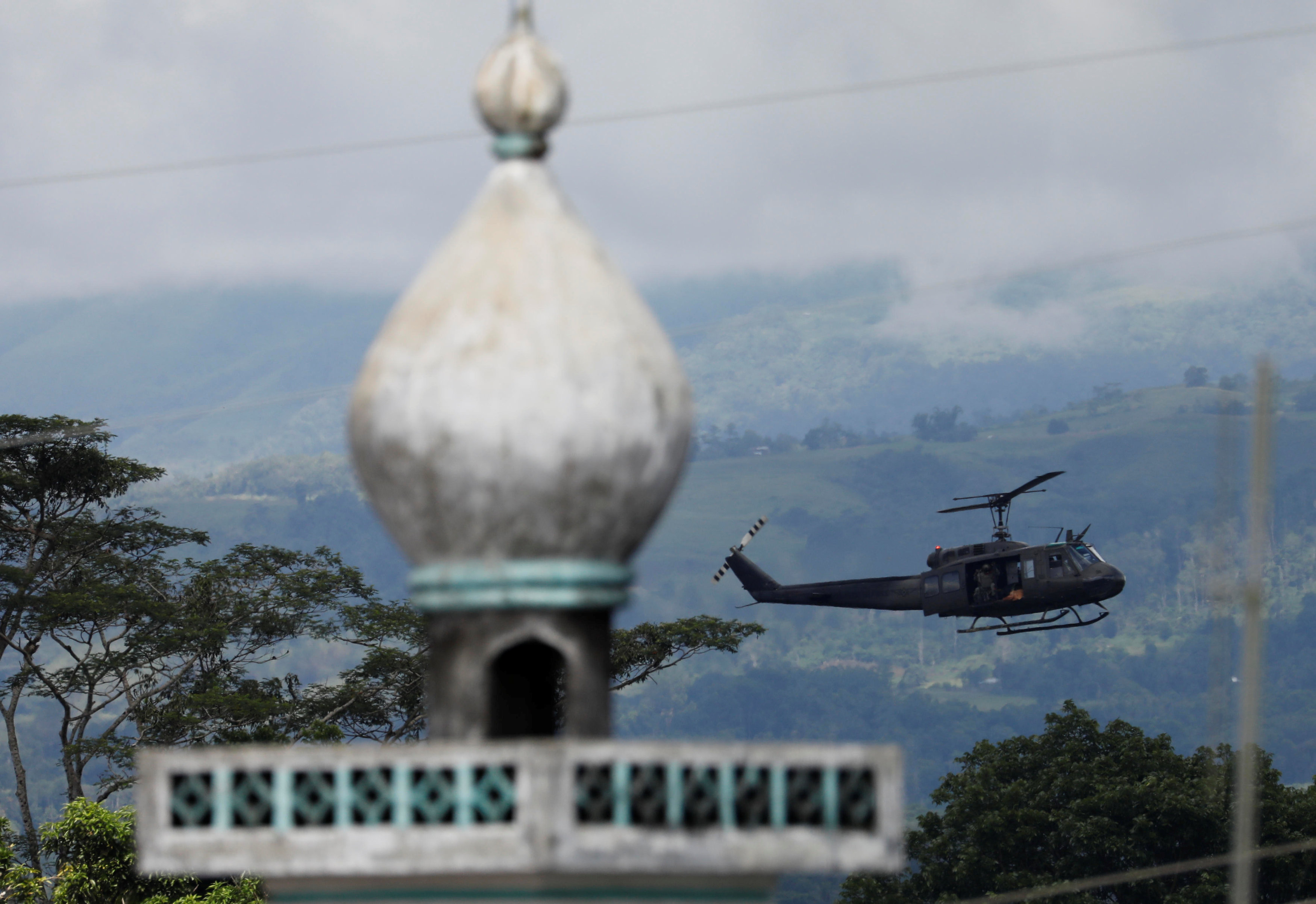 A military helicopter flies past a mosque in Marawi. Photo: Reuters