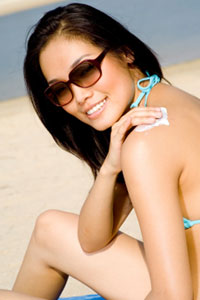 woman using suntan lotion