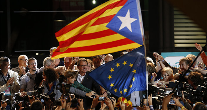 A estelada or pro independence flag and a European Union flag are waved in front of the President of Democratic Convergence of Catalonia Artur Mas, center in front of supporters in Barcelona, Spain, Sunday Sept. 27, 2015