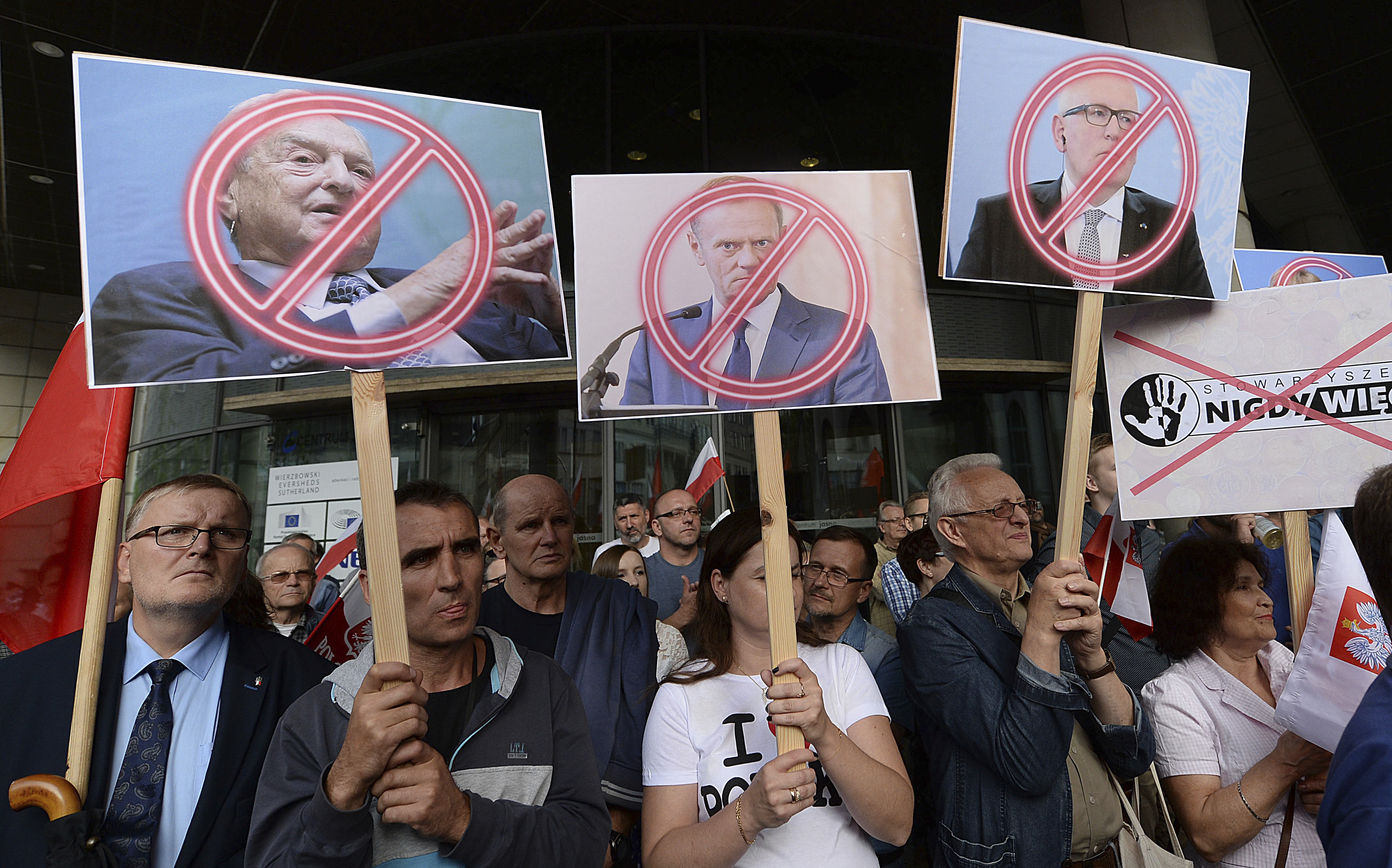 People demonstrate, outside the office of the ruling party leader Jaroslaw Kaczynski, holding banners with the images of from left, financier George Soros ,President of the European Council Donald Tusk and First Vice-President of the European Commission Frans Timmermans, during a protest, in Warsaw, Poland, Wednesday, July 26, 2017
