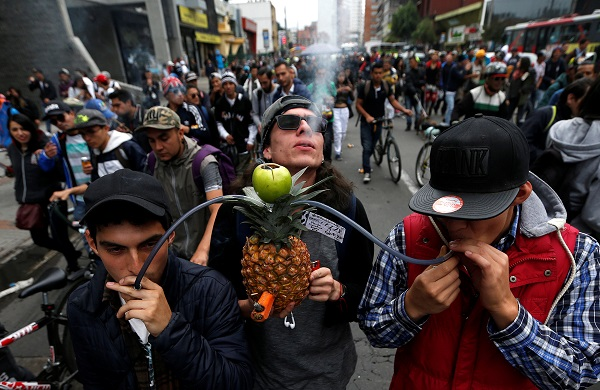 Men smoking cannabis through a pineapple during the Global March for Marijuana in Bogota, Colombia.