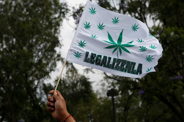 A participant holds up a flag during a march through the streets in support of the legalization of marijuana in Mexico City. The words on the flag read: