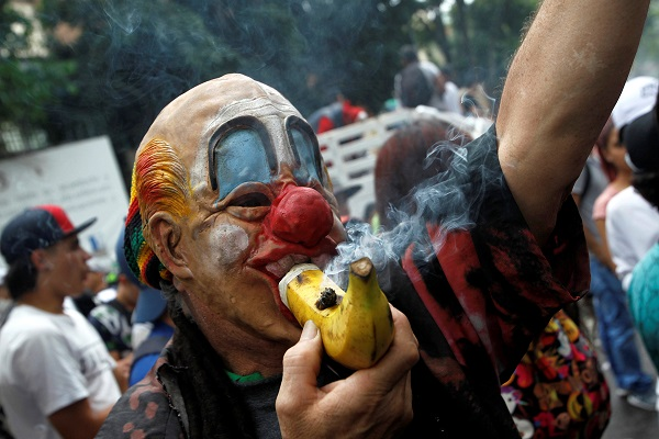 A man smokes weed through a banana during the Global March for Marijuana in Medellin, Colombia.