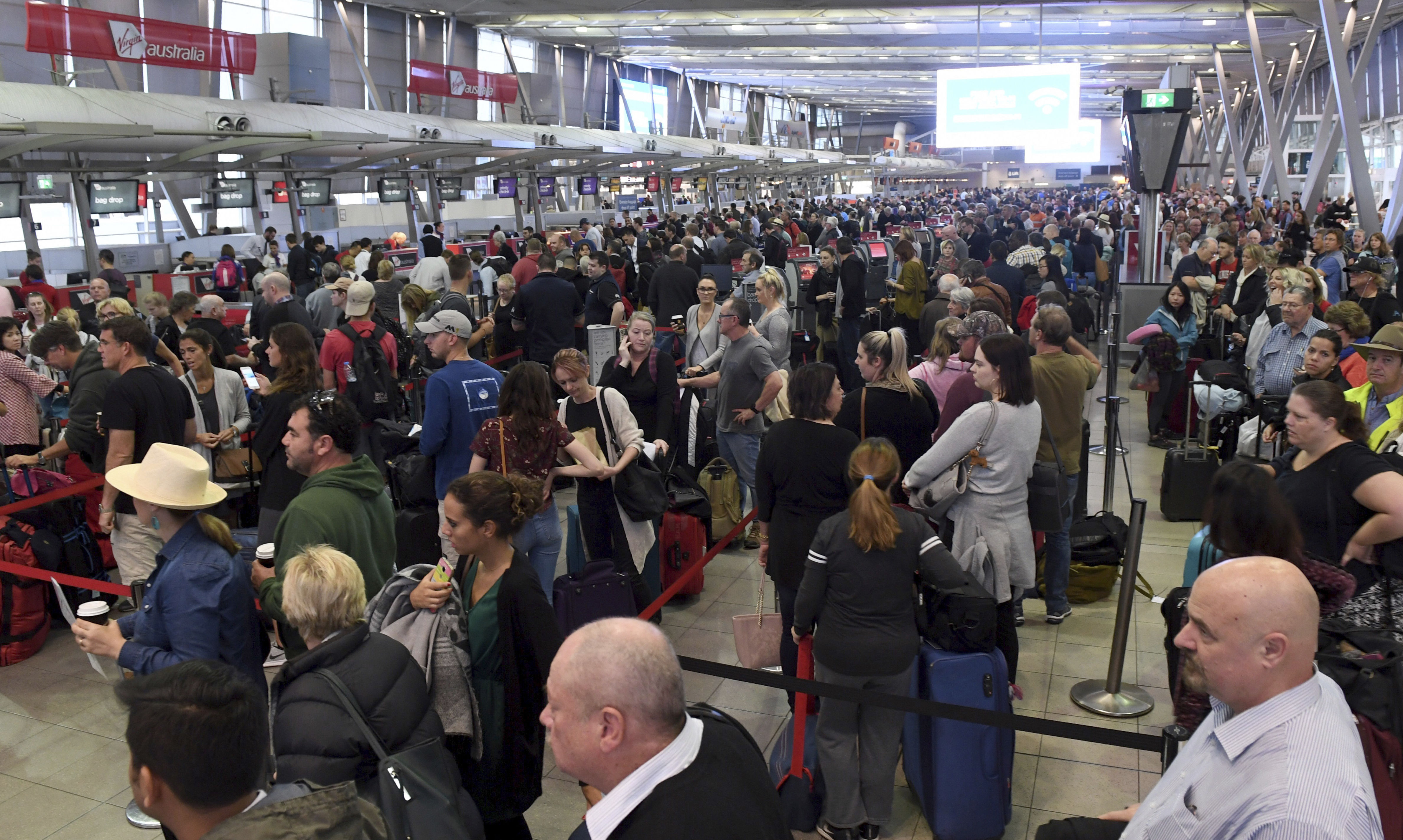 People crowd a terminal at Sydney's domestic airport as passengers are subjected to increased security, in Sydney, Australia, Monday, July 31, 2017. Security remains heightened in airports around Australia with more intense screening of luggage after law enforcement officials said they had thwarted a plan to bring down an airliner.