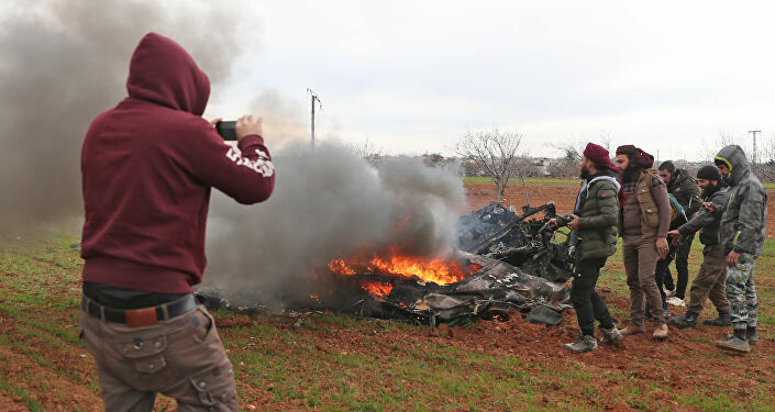 Syrian rebel fighters gather around the burning remains of a military helicopter after it was shot down over the village of Qaminas, about 6 kilometres southeast of Idlib city in northwestern Syria on February 11, 2020