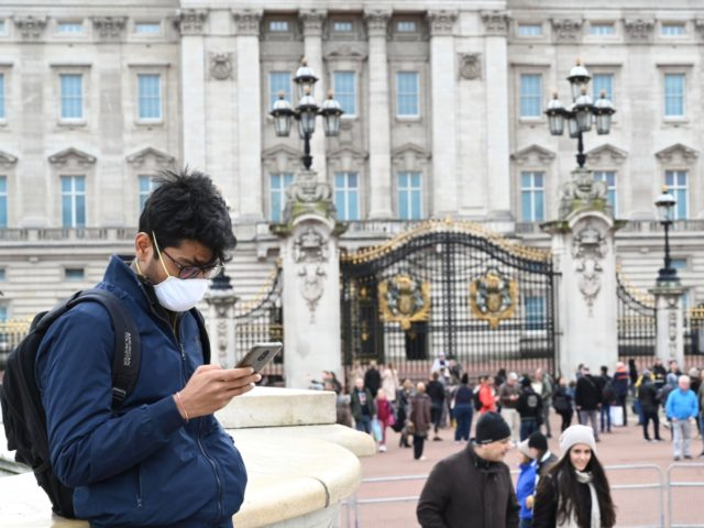 A tourist wearing a mask checks his cellphone in front of Buckingham Palace in London on March 14, 2020. - British Prime Minister Boris Johnson, who has faced criticism for his country's light touch approach to tackling the coronavirus outbreak, is preparing to review its approach and ban mass gatherings, …