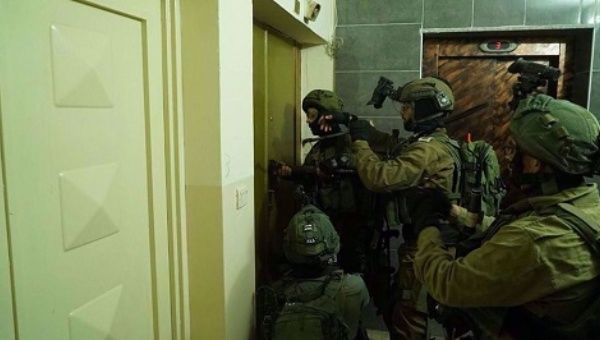 An undated photo by Palestinian media shows Israeli forces breaking into a Palestinian home.