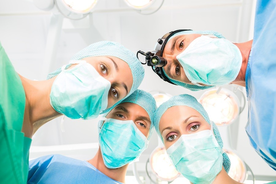 Hospital - surgery medical team of doctors in operation room or Op operating on patient in an emergency